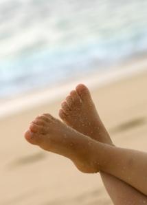 los pies de un niño de vacaciones en la playa