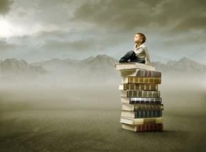 niño subido a una montaña de libros